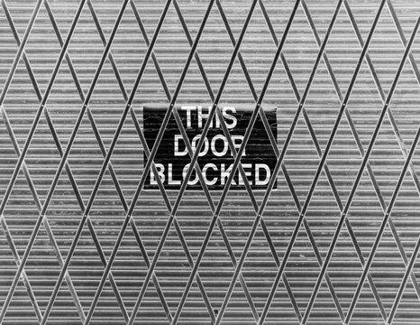 """This Door Blocked"""" sign on loading zone doorway"""