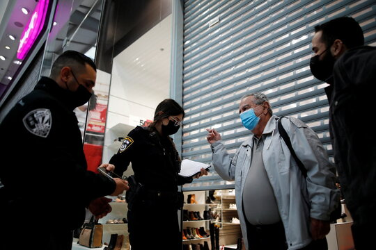 Israeli police question a man in front of a shop that reopened its doors in defiance of coronavirus disease (COVID-19) restrictions, at a mall in Petah Tikva