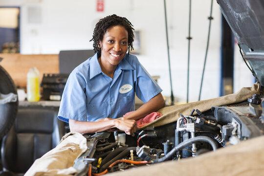 Portrait of smiling black female mechanic in auto repair shop