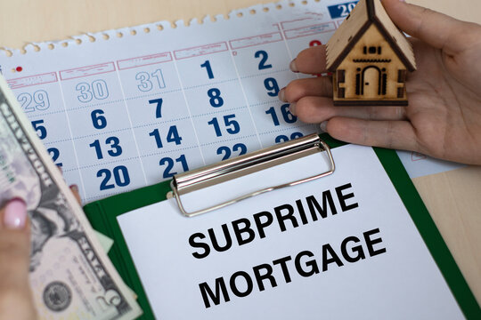 SUBPRIME MORTGAGE - word in a folder against the background of women's hands with a house and money