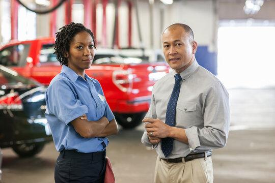 Male Pacific Islander auto repair shop manager talks to female Hispanic mechanic