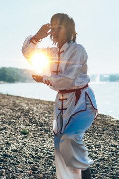 Digital Composite Of Mature Woman Practicing Martial Arts At Lakeshore Against Sky