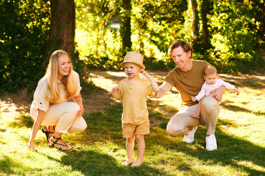 Outdoor portrait of happy family having fun in summer park, young couple with toddler boy and baby girl