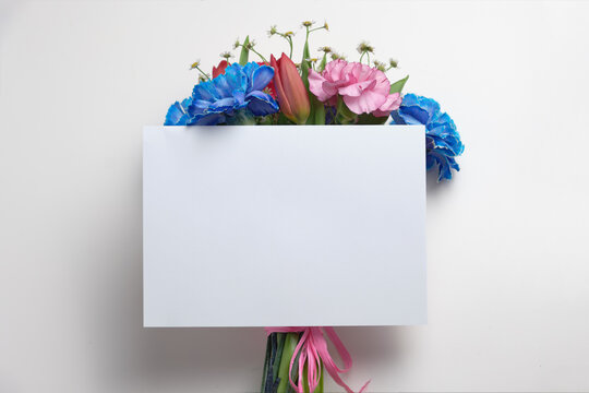 A white mockup of an invitation card with a bouquet of beautiful colorful flowers on a gray table. the ratio is 5x7, similar to A6, A5.