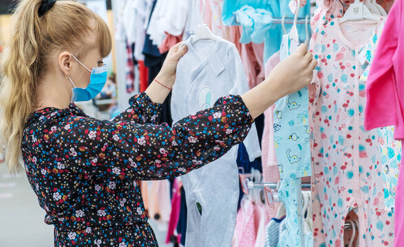 Woman chooses baby clothes in the store. Selective focus.