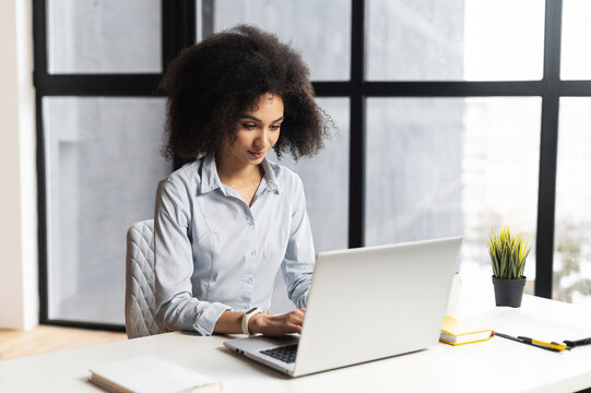 Side view of focused African American female office worker with Afro hairstyle sitting at the desk against panoramic window, working on project, typing on the laptop, concentrated on clients problem