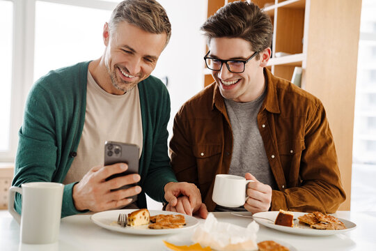 Happy caucasian gay couple using mobile phone while having breakfast