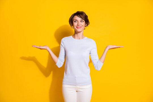 Photo of charming lady raise two palms look empty space wear white shirt trousers isolated yellow color background