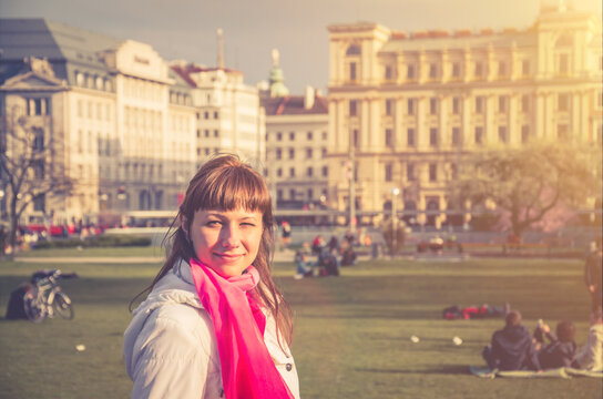 Young girl traveler with white jacket looking away and smile in Sigmund Freud Park of Vienna city historical centre with old buildings background, woman on vacation in Austria, backlit sun flare