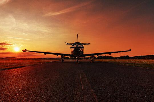 A single-engine plane is parked on the runway, bathed in the evening sun. Beautiful color view of the plane.