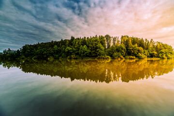 Scenic view of trees reflecting on the calm lake under a clouds sky during sunset