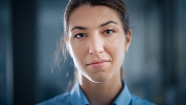 Beautiful Female in Blue Casual Shirt Calmly Looks at Camera. Her Occupation May be a Doctor, Surgeon, Succesful Entrepreneur or Manager. Covid-19 Pandemic Concept.