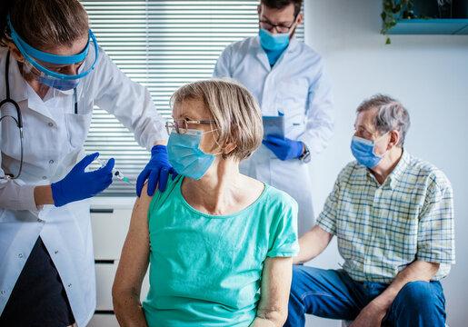 medical team giving coronavirus vaccine to seniors in vaccination center
