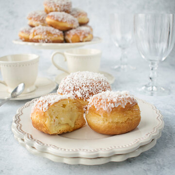 Donuts with frosting and coconut and white chocolate pudding filling. Appetizing sweet cakes on a white plate.