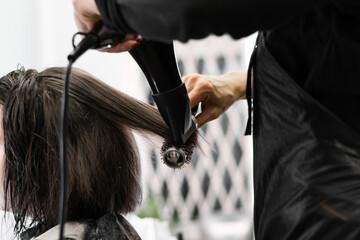 Fototapeta Hairdresser Using Dryer on Woman Wet Hair in Salon. Short Hair. Hairstyle styling on a round brush, black and white range of beauty salon,