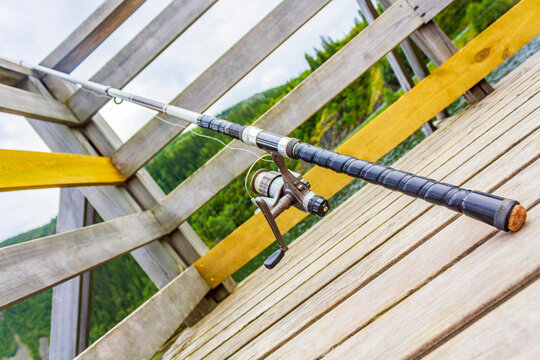 Fishing rod on wooden pier by the lake Vang Norway.