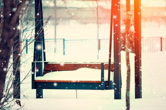 Empty swing in the park on a winter day. Beautiful winter landscape.