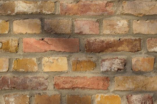 Mauer aus recycelten alten gelb-orangenen Backsteinen