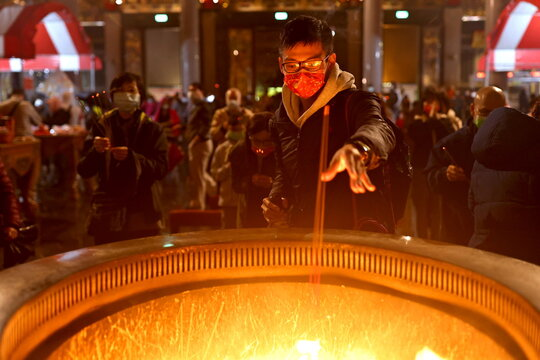 A man throws incense sticks into the fire while wearing a protective mask to prevent the spread of the coronavirus disease (COVID-19) during a Lunar New Year prayer at a temple in Taipei