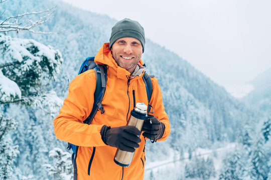 Laughing Man dressed bright orange softshell jacket with a hot drink thermos flask looking at camera while he trekking winter mountains route. Active people in the nature concept image.