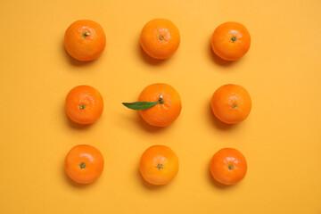 Fresh ripe tangerines on orange background, flat lay