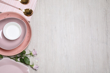 Flat lay composition with beautiful dishware and roses on white wooden table. Space for text