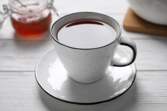 Cup of fresh tasty tea on white wooden table