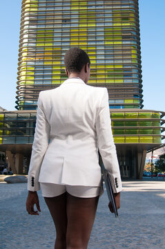 Afro-European business woman in the commercial area of the city under a sunny day doing business