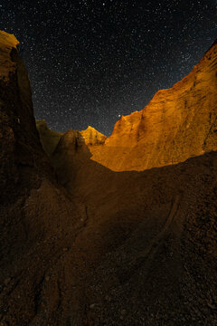 Canyon with a starry sky at night with a moonlit section.