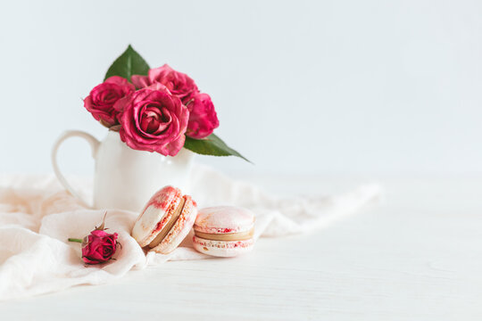 Tasty french macaroons with pink roses on a white background.
