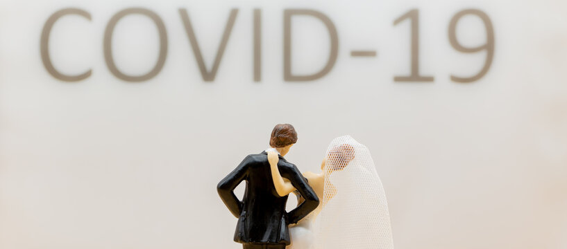 Bride and husband standing in front of a lettering with covid 19, celebrating without party guests because of corona