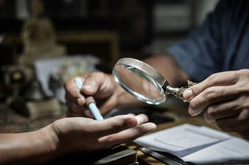 Close-up Of Man Looking Person Hand With Magnifying Glass