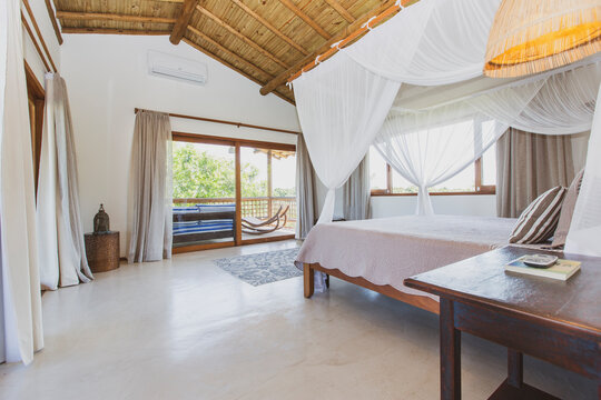 Modern luxury summer holiday or vacation wooden beach house bedroom interior with rustic canopy bed, white transparent curtains and glass door to the balcony.