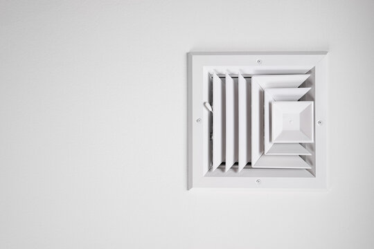 Photograph of a residential ceiling heating and cooling vent painted white