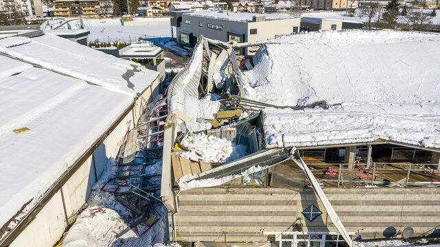 The roof collapsed under the weight of snow. Aerial view of damaged falling roof inside a publica city area. Large collapsed condominium or industrial company. View from above with a drone.