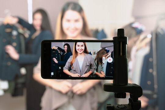 Group of beautiful Asian female influencers using smartphone to streaming live video showing new clothes and communicate with audience. Online business marketing, Fashion, Selling on Social media.