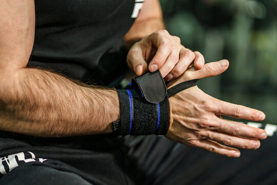 Close up on hands of unknown man holding and putting on and adjusting wrap bandages on wrists for powerlifting body building training sport equipment at the gym