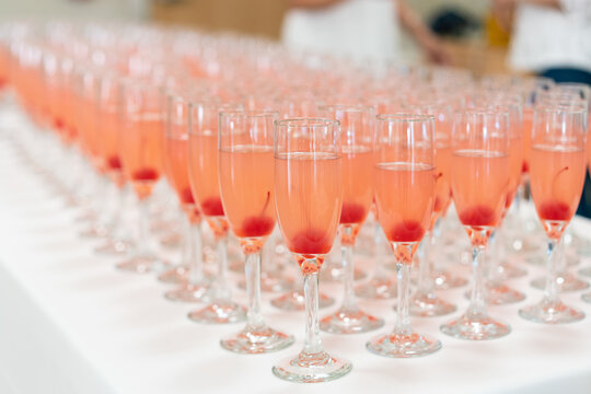 Row of champagne glasses with red maraschino cherries on a table