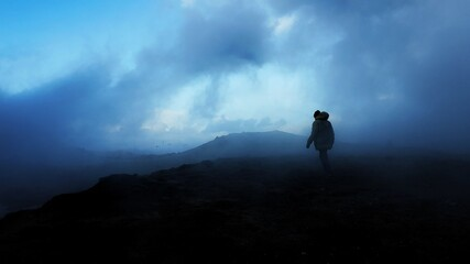 Silhouette Person Standing On Mountain Against Cloudy Sky