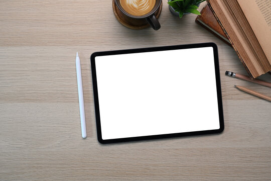 Above view of digital tablet with empty screen, stylus pen, coffee cup and notebook on wooden table.