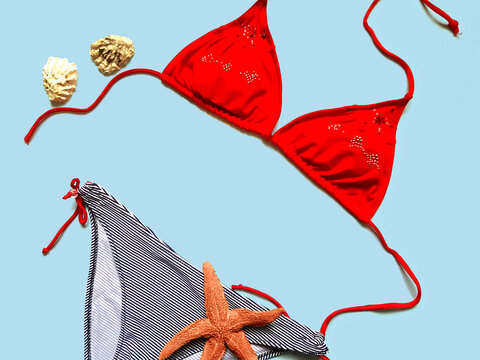 Fashionable bikini swimsuit flat lay on blue background, copy space. Summer vacation concept