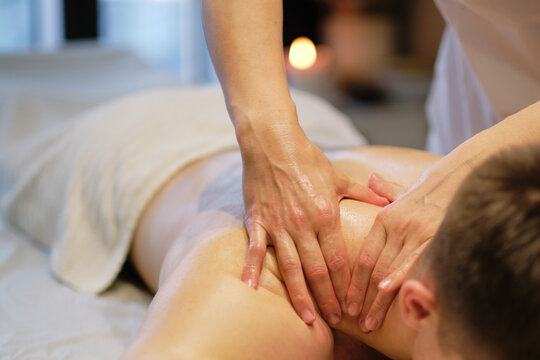 Close-up of man enjoying in relaxing shoulders massage . Man relaxing on massage table receiving massage