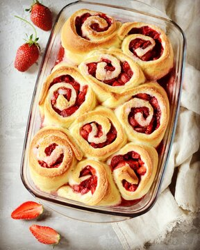 Homemade yeast buns with strawberries on gray background