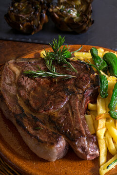 Grilled ribeye beef steak served with rosemary on wooden table