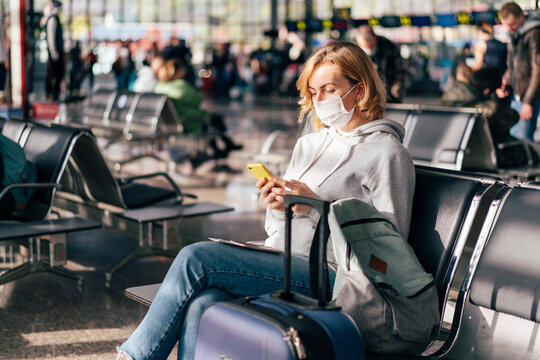 A European woman in a protective medical mask on her face sits at the airport waiting for a flight and uses the phone.