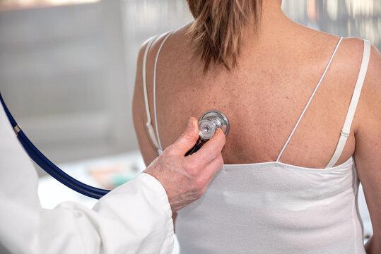Doctor using stethoscope to exam patient