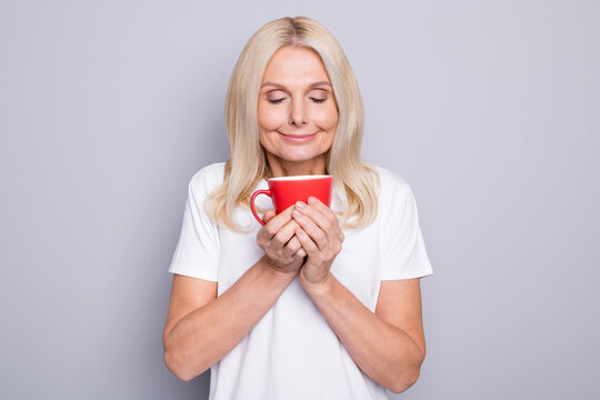 Photo portrait of old woman inhaling smell of nice morning coffee holding red cup in two hands isolated on grey colored background