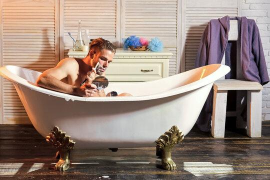 Bearded man with shaving soap look in mirror. Guy with beard shave beard with razor in bathtub in bathroom.