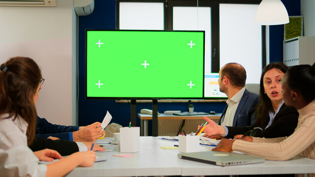 Group of business people discussing company plan with mockup tv green screen in front of desk, ready for financial project presentation. Multiethnic team using mock up monitor with chroma key display