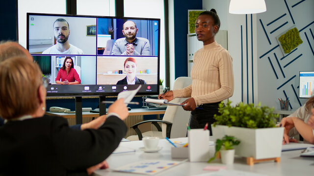 African woman discussing with remote managers on video call presenting new partners on webcam. Confident businesspeople talking to web cam streaming webcast training, doing online conference call.